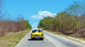 A solitary yellow taxi on the rural roads of Cuba.