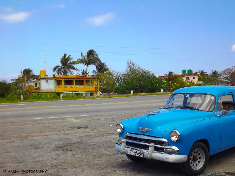A blue Chevrolet in the middle of an empty road. There is a yellow wooden house in the background.