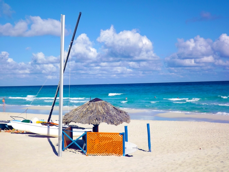 A palm beach parasole on the white sands of Varadero beach