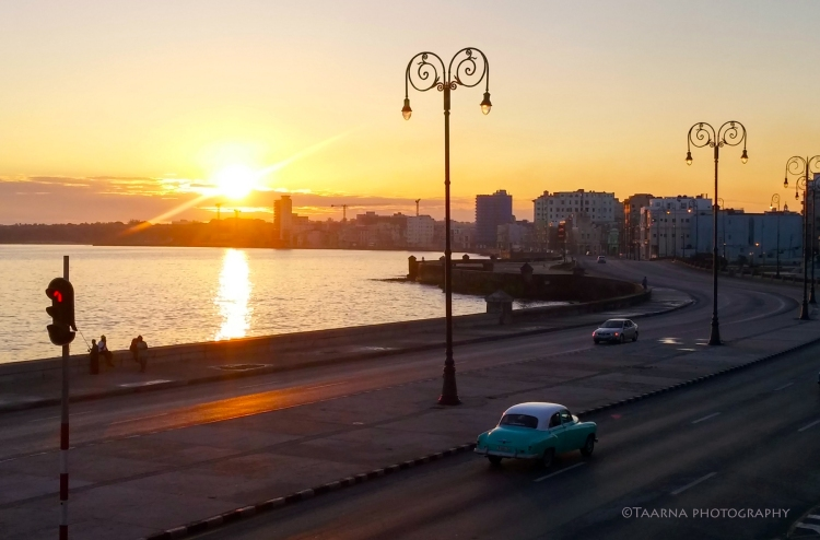 Sun rising over Malecon, Havana. It is early morning and there are only two cars one the road, one of which is a mint coloured 1951 Chevrolet.