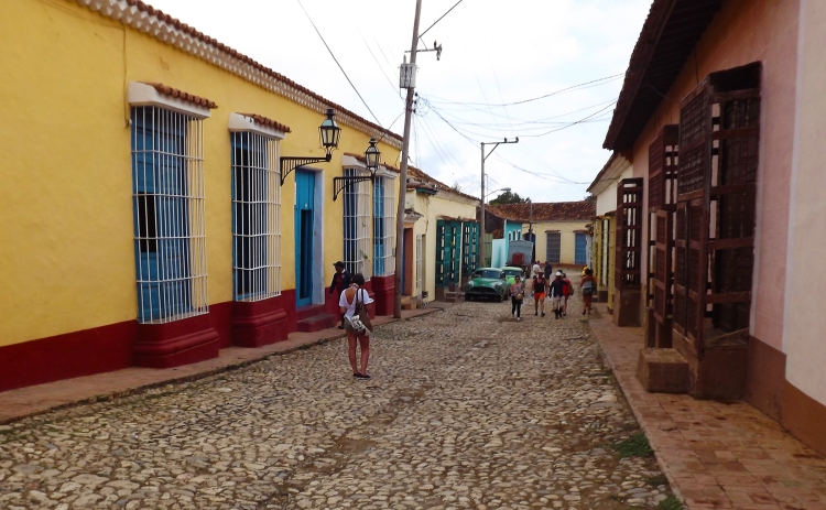 A view down the cobbled street of Trinidad. The street is passing next to houses with big windows with wrought iron grills.