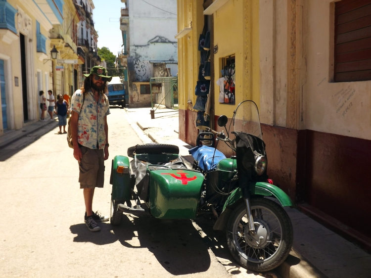 The husband posing next to a dark green Ural motorcycle with a side car. The sidecar's front has a painted on red hammer and sickle.