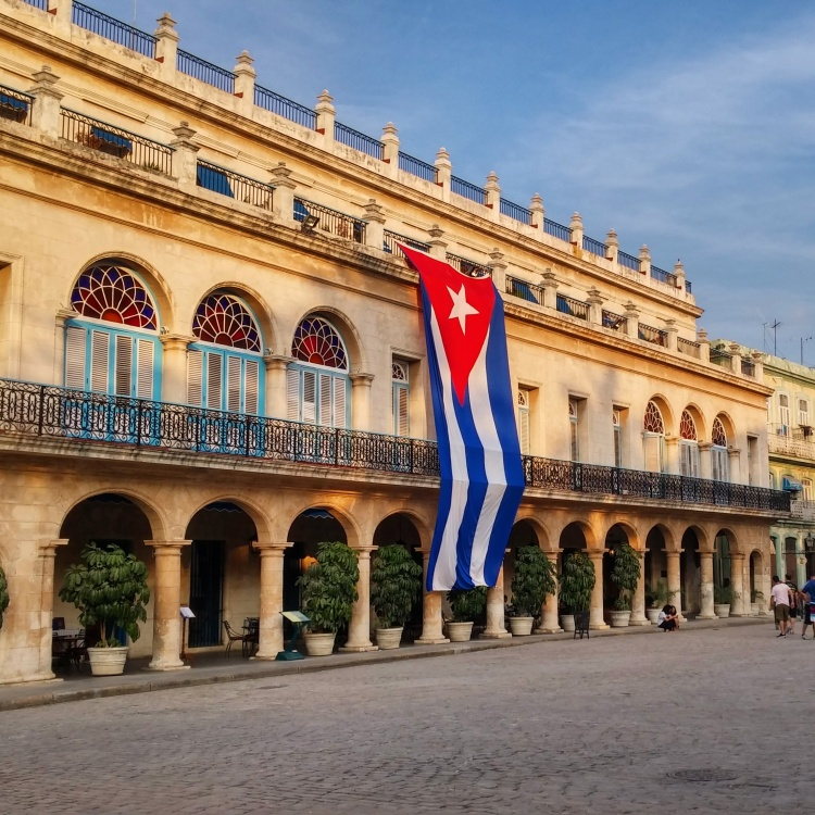 A big Cuban flag is hanging from the balcony of an old, elegant building on Plaza e Armas, Havana.