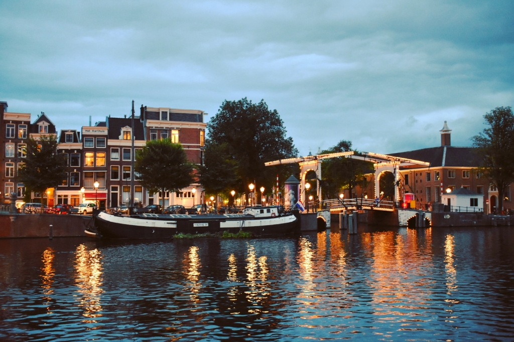 An iconic representation of Amsterdam - the canal with a bridge and a barge at dusk.