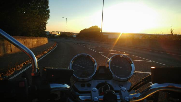 Looking at the sunset over the motorcycle handbars. The empty road is in front.
