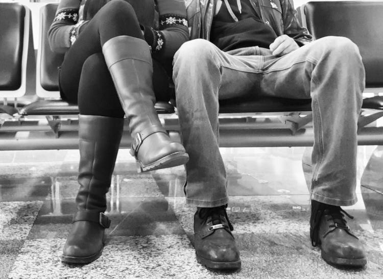 Black and white photo of us, legs only, waiting at Ljubljana airport