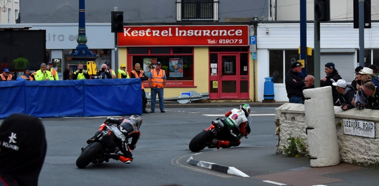 Two superbike races are rounding a 90 degree corner at Ramsey, Isle of Man.
