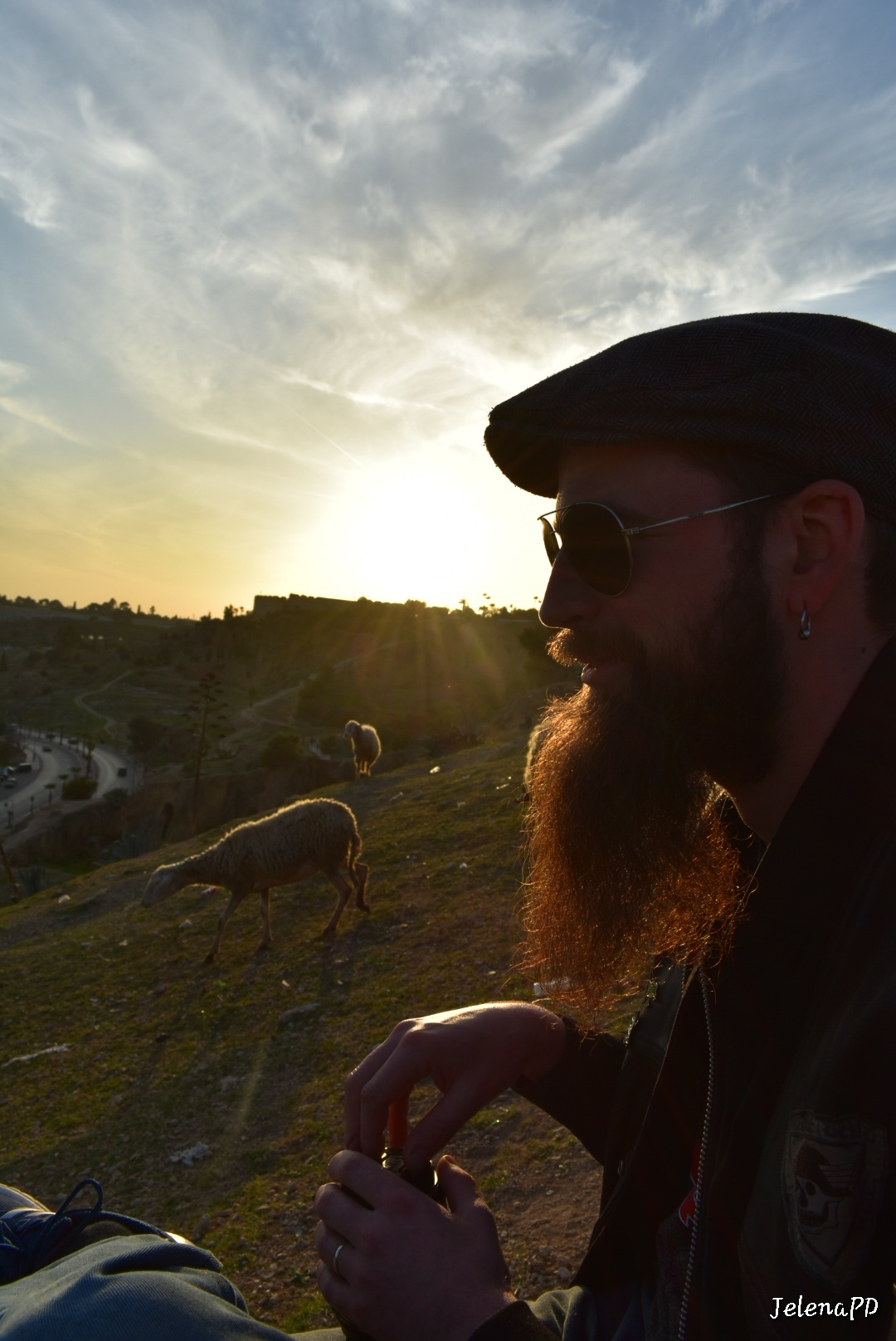 A silhouette of a man in profile. The sunlight is shining through his beard.