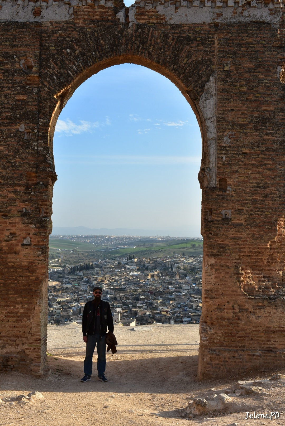 A man standing under the stone archway with Fes in the background.
