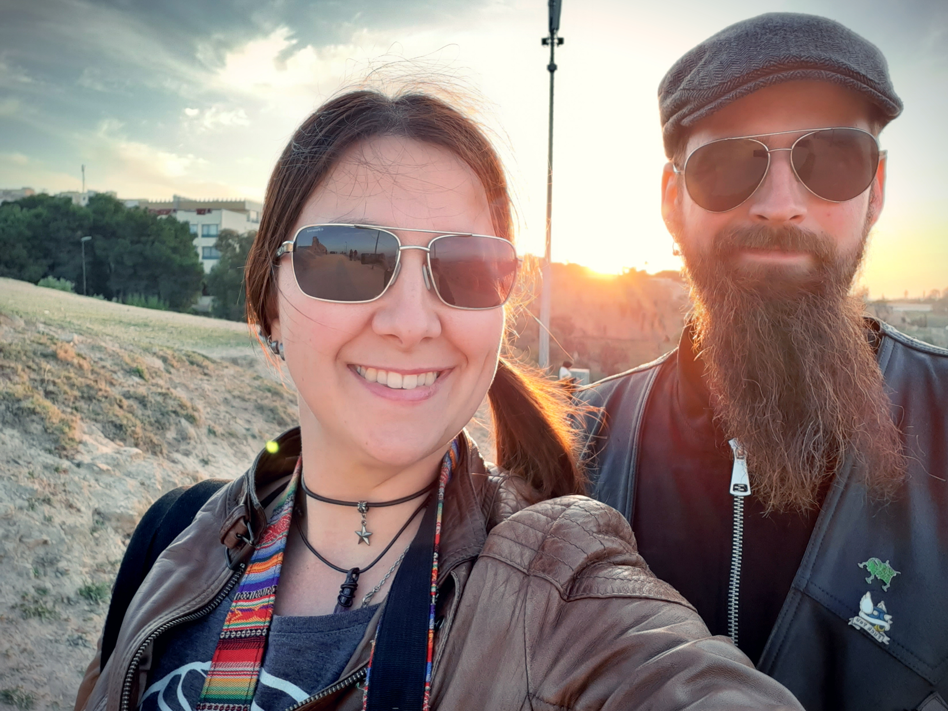 A selfie of the travelling couple. The sun is setting in the background.