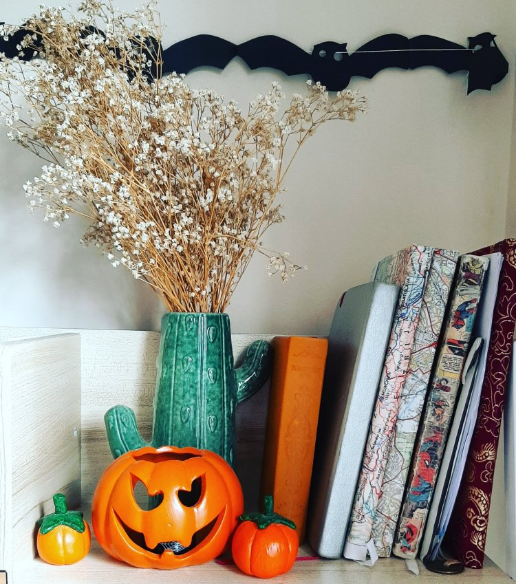 Halloween decoration on my desk - three clay pumpkins, books on the right and bats hung up on the wall.