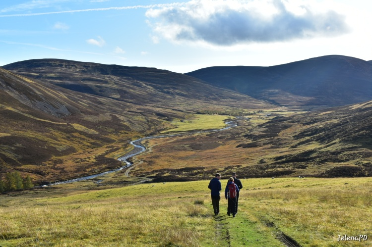 The view of the Cairngorms hill in autumn. A stream is flowing through the valley and there are three people walking away from the camera.