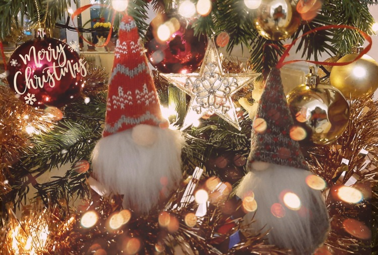 Two Christmas gnomes in the middle of a decorated Christmas tree.