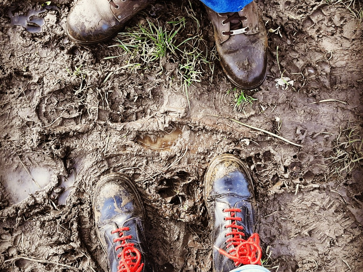 From my point of view, photo of our boots covered in muddy on an extremely muddy path.