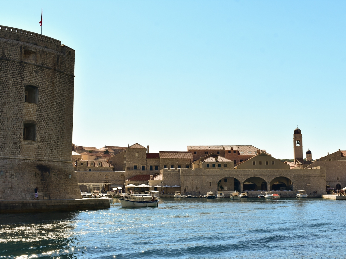 Photo of Dubrovnik dock and fortification walls taken from a boat.