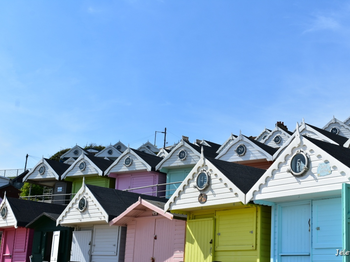 Colourful beach huts at Frinton-on-Sea with the clear blue sky behind them