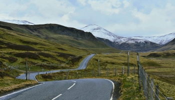 An empty twisty road going through the Scottish highlands